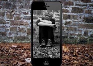 smutny chłopiec widziany przezsmartphone